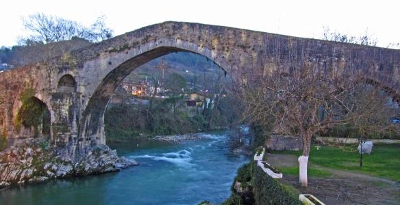 Romaanse brug in Cangas de Onis met onder de brug het Cruz de Victoria.