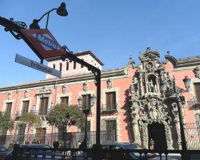 Het Museo de Historia, voorheen was dit het Real Hospicio del Ave María y San Fernando, gezien vanaf de ingang van het metrostation de Tribunal in Calle Fuencarral. Het smeedwerk, samen met de ´fernandinas´lampen, van deze metro ingang is van Antonio Palacios (1919), het is één van het alomtegenwoordige straatmeubilair in Madrid. Beide vormen enkele van de hoogste uitingen van de late Spaanse barok: De ingang van het Hospicio, werk van Pedro de Ribera, gebouwd tussen 1722 en 1726. Het zou beter passen bij een aristocratisch paleis dan bij dit benedicteinachtige hofje. Het was opgezet om 3000 bewoners te vestigen en dit oorspronkelijke doel werd tot 1922 nagekomen. daarna werd het werd op initiatief van de Real Academia de San Fernando gered van de ondergang, door het om te bouwen tot het Museo del Historia dat staat in het epicentrum van het nachtleven in de wijk Malasaña.