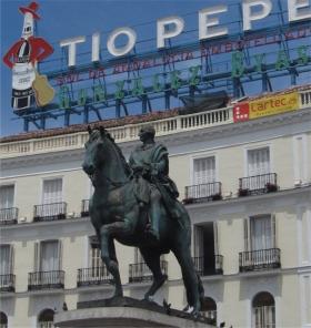 """Standbeeld van Carlos III die ook wel """"de beste burgemeester van Madrid"""" werd genoemd. Op de achtergrond de nieuwe plaats van de wereldberoemde Tio Pepe neonreclame."""