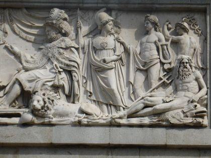 Fernando VII ontvangt hommages van Minerva en Schone Kunsten, reliëf dat het (westerse) Dorische portiek van het Museum bekroont. Het detail toont de rechterkant van de fries, gebeeldhouwd door Ramon Barba en werd aangevuld door zijn assistenten, enkele jaren na zijn dood. We zien de koning Fernando VII, omringd door Minerva, Apollo, Mercurius en Neptunus.