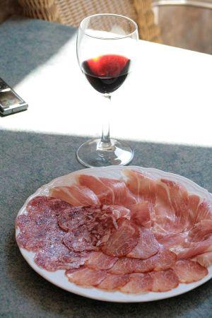 Vino tinto, rode wijn met een schaal Iberische vleeswaren.